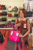 Woman buying handbags. Woman in handbag shop happy buying bags in sale stock photo