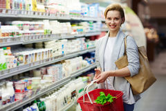 Woman Buying Healthy Food in Grocery Store. Portrait of beautiful blond woman with shopping basket buying groceries in supermarket and smiling looking at camera royalty free stock image
