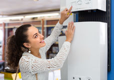 Woman buying heating water boiler Stock Photography
