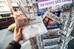 Woman buying international press with Emmanuel Macron and Marine Stock Images