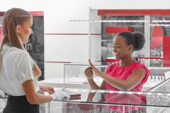 Woman buying jewelry at the store. Shot of a happy African young women smiling joyfully trying on rings at the jewelry store royalty free stock images