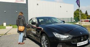 Woman buying luxury race car Maserati Ghibli stock video