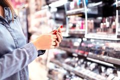 Woman buying make up at cosmetics section in store. Customer shopping beauty products. Choosing red lipstick from shelf. stock photo