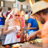 Woman buying a meal at food market. Stock Images