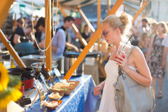 Woman buying meal at street food festival. Royalty Free Stock Photography