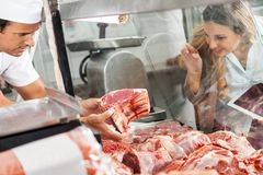 Woman Buying Meat At Butchery Stock Photo
