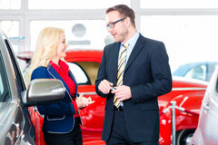 Woman buying new car. In auto dealership Stock Photography