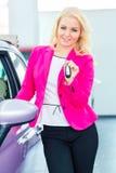 Woman buying new car at dealership showing key. Woman buying car at dealership and holding key in hand Stock Image