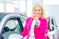 Woman buying new car at dealership showing key Royalty Free Stock Image