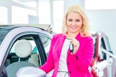 Woman buying new car at dealership showing key. Woman buying car at dealership and holding key in hand Royalty Free Stock Image
