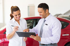 Woman buying new car. Happy women buying a new car at vehicle showroom Royalty Free Stock Image