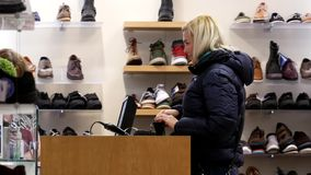 Woman buying new shoes and chatting with clerk. At check out counter stock video