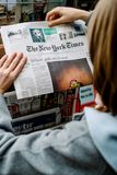 Woman buying The New York Times newspaper. STRASBOURG, FRANCE - OCT 28, 2017: Woman buying The New York Times newspaper business at press kiosk featuring article royalty free stock photography