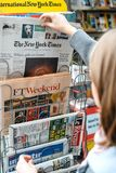 Woman buying The New York Times newspaper royalty free stock image