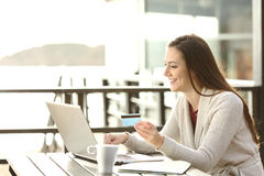 Woman buying online or booking hotel. Portrait of a woman buying on line or booking hotel with a laptop and credit card on the beach in vacations. E commerce stock images