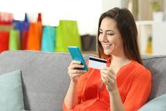 Woman buying online with credit card and cellphone. Sitting on a couch in the living room at home Royalty Free Stock Photo