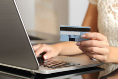 Woman buying online with a credit card ecommerce. Close up of a woman hands buying online with a credit card and a laptop. Ecommerce concept Stock Image