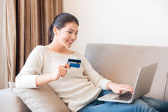 Woman buying online on laptop computer with credit card Royalty Free Stock Photography