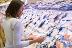 Woman buying pack of salmon