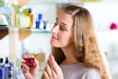 Woman buying perfume in shop or store Royalty Free Stock Photos