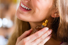 Woman buying perfume in shop or store Stock Image