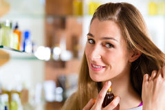 Woman buying perfume in shop or store Stock Photo