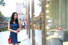Happy Asia Chinese Eastern oriental young trendy woman girl shopping in mall with bags look at shopping window on street city Royalty Free Stock Images