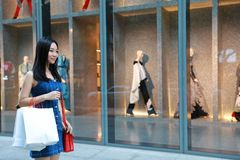 Happy Asia Chinese Eastern oriental young trendy woman girl shopping in mall with bags shopping window background on street city Stock Images