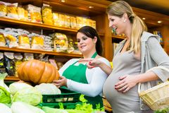 Woman buying pumpkin and vegetables in delicatessen stock photography