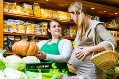 Woman buying pumpkin and vegetables in delicatessen Stock Image