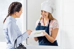 Woman Buying Ravioli Pasta Packet From Female Chef Royalty Free Stock Images