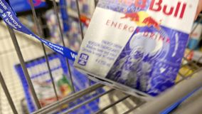 Woman buying Red Bull energy drink and putting into shopping cart stock video