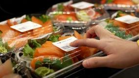 Woman buying salmon sashmi stock footage