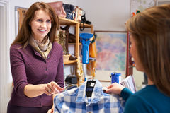 Woman Buying Shirt In Charity Shop. Volunteer In Charity Shop With Customer Buying Clothes Royalty Free Stock Photography