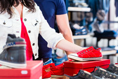 Woman buying sneakers shoes Royalty Free Stock Photos