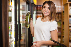 Woman buying some green water. Cute young woman buying some water with chlorophyll at a grocery store Royalty Free Stock Photos