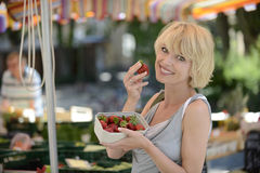 Woman buying strawberries at farmer's market. Happy woman buying strawberries at farmer's market Royalty Free Stock Photography
