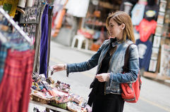 Woman buying in a street market. A young woman is looking some objects in a street market. She is relaxed Stock Images