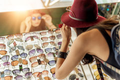 Woman buying sunglasses. Happy woman buying sunglasses in shop on the street Stock Photography