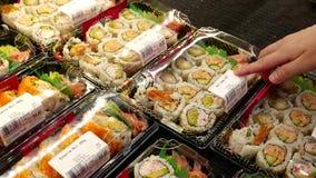 Woman buying sushi roll combo