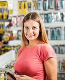 Woman Buying Tools In Hardware Store. Portrait of happy mid adult woman buying tools in hardware store Royalty Free Stock Photos