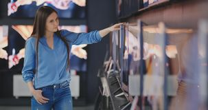 Woman buying TV in a store. 4K UHD.
