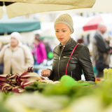 Woman buying vegetable at local food market. Royalty Free Stock Images
