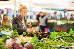 Woman buying vegetable at local food market. Royalty Free Stock Photos