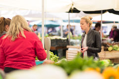 Woman buying vegetable at local food market. Royalty Free Stock Image