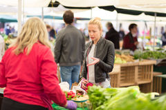Woman buying vegetable at local food market. Royalty Free Stock Photography