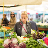 Woman buying vegetable at local food market. Stock Photos