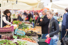 Woman buying vegetable at local food market. Woman buying fruits and vegetables at local food market. Market stall with variety of organic vegetable stock photo
