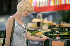 Woman buying vegetables at farmer's market. Happy woman buying vegetables at farmer's market Royalty Free Stock Image