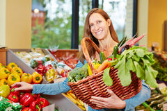 Woman buying vegetables in organic food store Stock Images